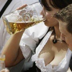 Mulher bebendo uma caneca de cerveja e homem observando