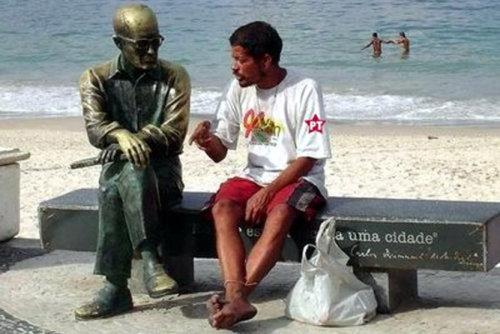 Bêbado conversando com estátua do Carlos Drummond