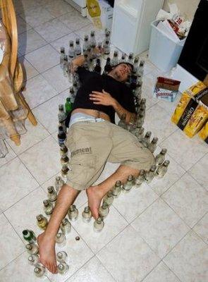 Bêbado dormindo cercado por garrafas