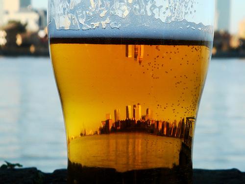 Copo de cerveja refletindo uma cidade