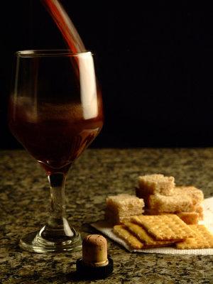 Taça de vinho com biscoitos ao fundo.