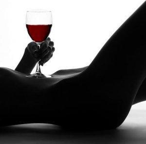 Mulher com uma taça de vinho em cima da barriga