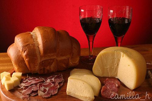 Taça de vinho com queijos ao fundo.