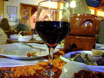 Taça de vinho com fondue ao fundo.