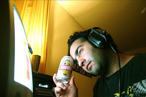 Bêbado na frente do computador e cerveja na mão