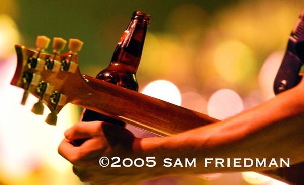 Homem tocando guitarra com garrafa de cerveja