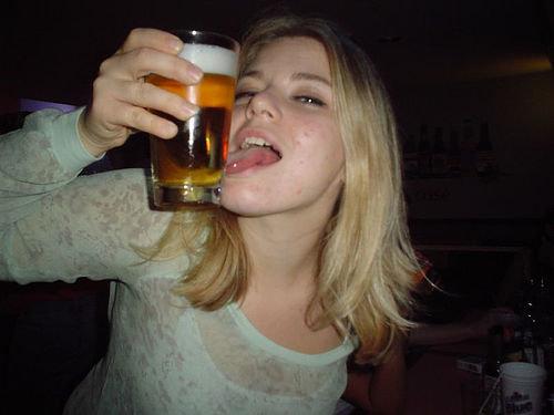 Mulher passando língua no copo de cerveja