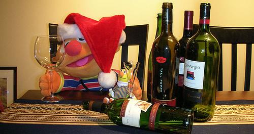 Boneco com gorro de natal e vinhos