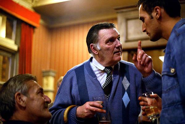 Três homens conversando no boteco
