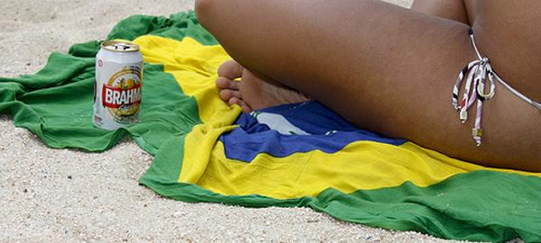 Mulher com uma cerveja sentada numa canga do Brasil