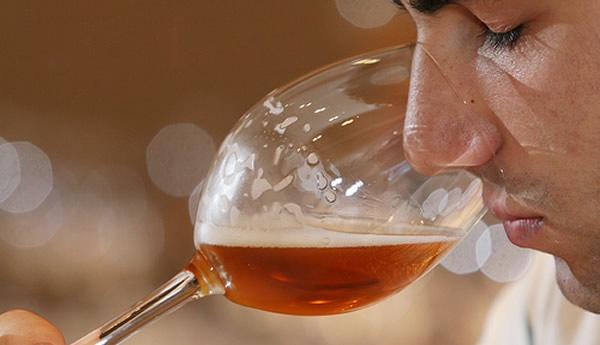 Homem degustando uma taça de cerveja
