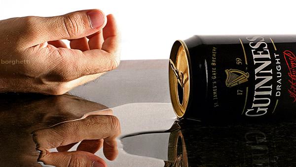 Mão caída e lata da cerveja Guinness
