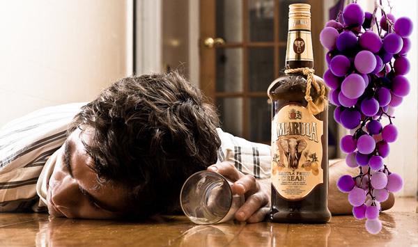 Bebado com uma garrafa de Amarula e cacho de uva