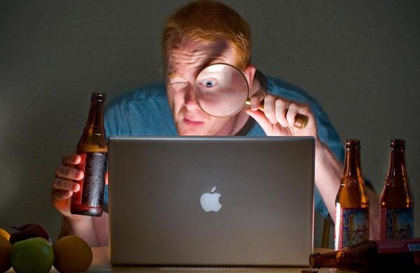 Homem com lente olhando pra um Laptop e com cerveja na mão
