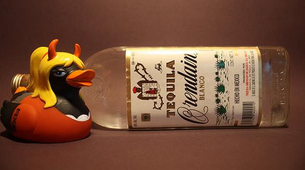 Boneca loira com chifres e uma garrafa de tequila