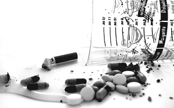 Cigarro, copo e remédios