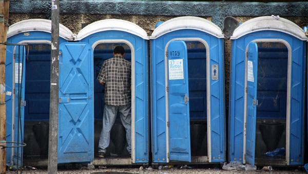 Homem mijando num banheiro químico