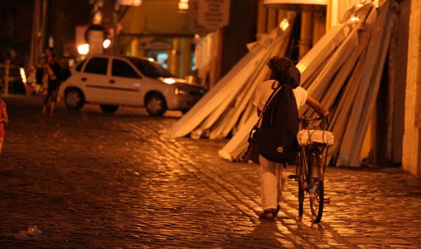 Pessoa indo embora levando a bicicleta