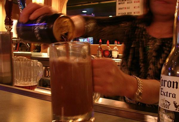 Mulher servindo um pint de Guinness