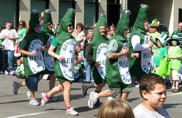 Pessoas fantasiadas de garrafas verdes da Guinness