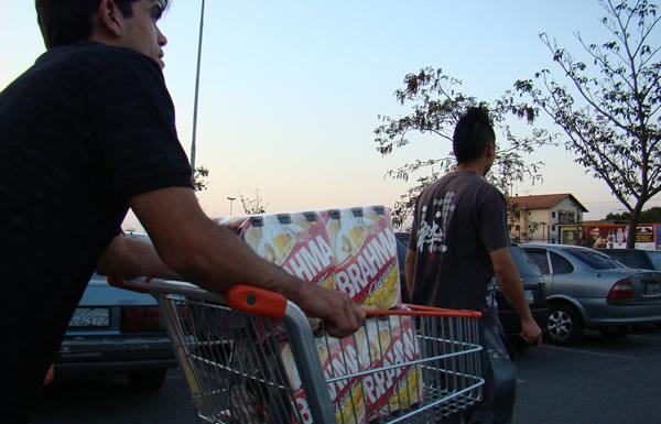 Homens levando carrinho de compras cheio de cerveja