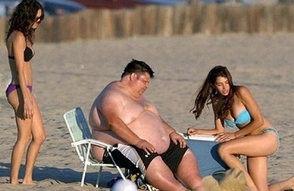 Gordo na praia com duas mulheres lindas