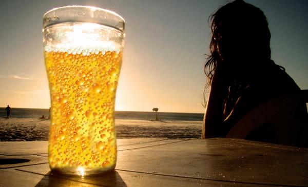 Copo de cerveja na frente do sol e mulher