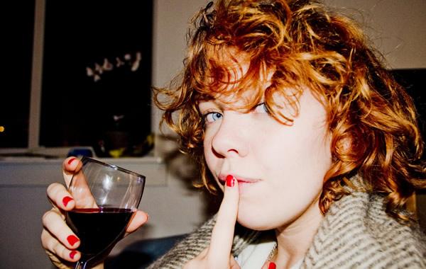Mulher bebendo vinho com dedo na boca
