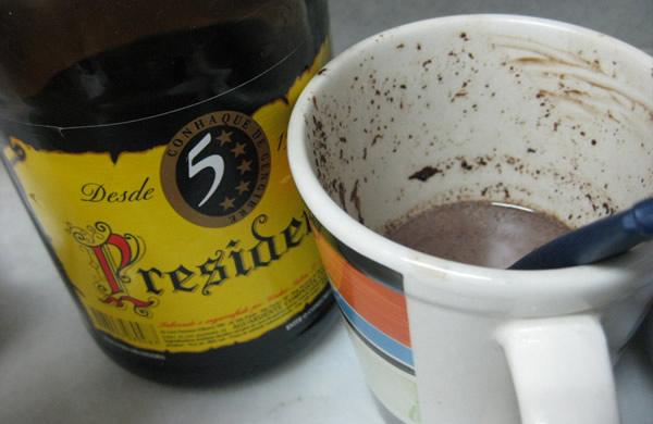 Garrafa de conhaque e xícara vazia de choconhaque