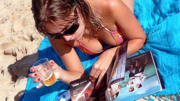 Mulher folheando revista na praia segurando copo de cerveja