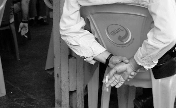 Homem sentado segurando um cigarro