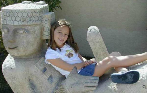 Garota sentada numa estáua com uma piroca