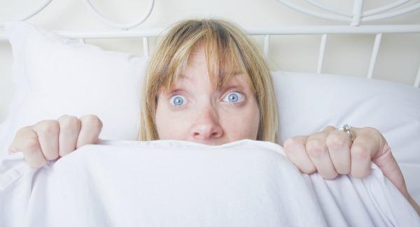 Mulher deitada na cama e assustada
