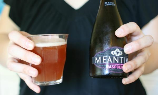 Mulher segurando garrafa e copo da cerveja Meantime