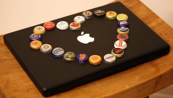 Macbook preto com tampinhas de cerveja em cima formando um coração