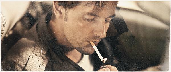 Homem fumando dentro de um carro