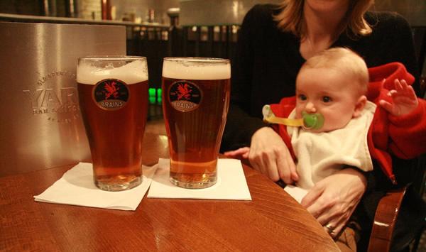 Bebê olhando copos de cerveja