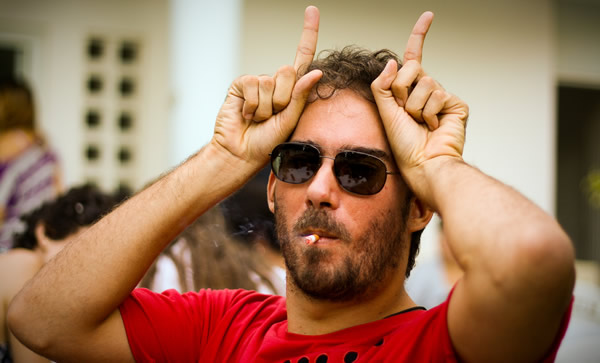 Homem fazendo chifre com os dedos