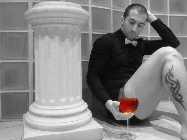 Cara em dúvida olhando taça de vinho