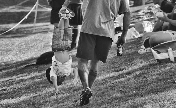 Pai carregando filho pelos pés