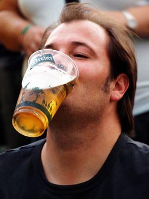 Homem segurando um copo de cerveja com a boca