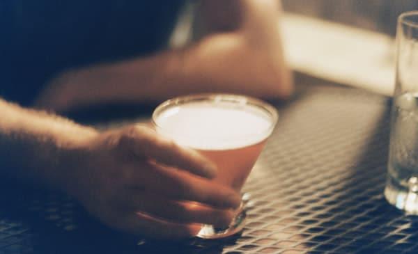Homem segurando copo do drink Manhattan
