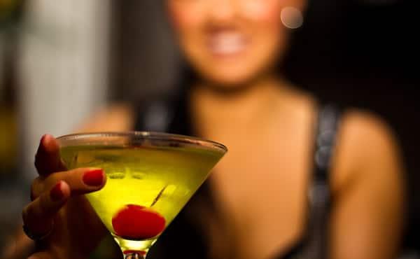 Mulher segurando taça de Apple Martini