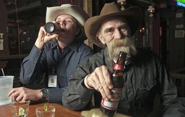 Amigos cowboys bebendo cerveja no bar