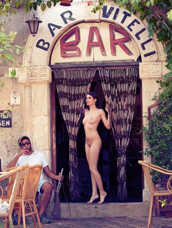 Mulher nua na entrada de um bar