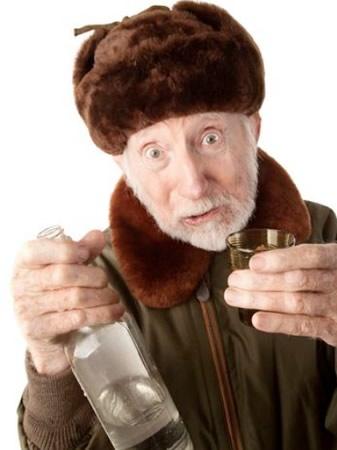 Velho segurando garrafa e copo de vodka