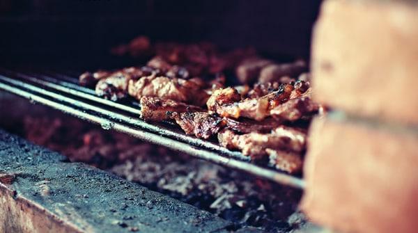 Churrasqueira acesa com carne sendo preparada