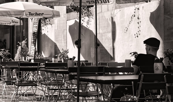 Homem sozinho sentado num boteco