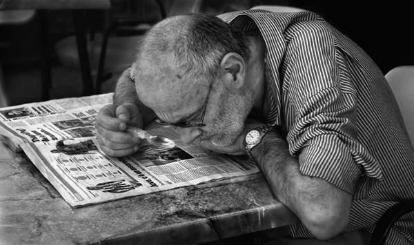 Idoso lendo jornal com lente
