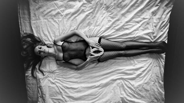 Mulher deitada segurando um mamão papaia
